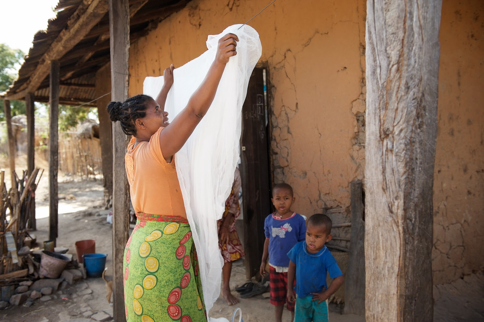 Florentine, a beneficiary from Boriziny, unfolds her newly delivered insecticide-treated bed net. / Lan Andrian, USAID Global Health Supply Chain Program — Procurement and Supply Management