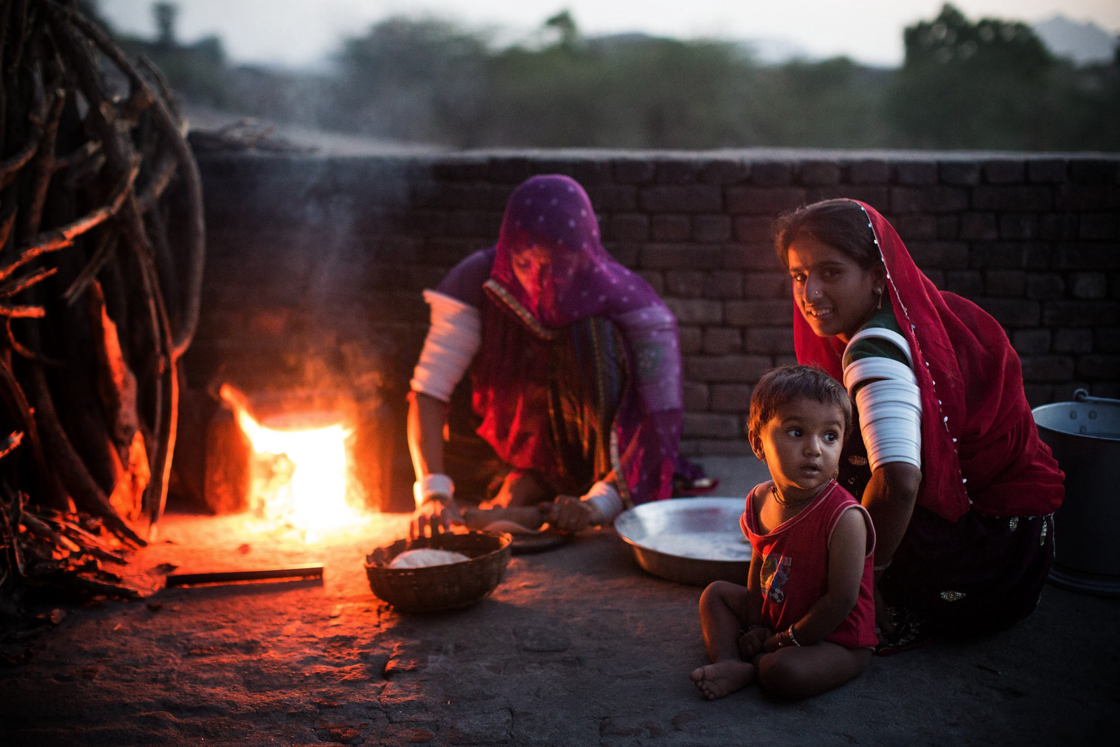 Mantra Ram and her sister roll out dough to bake chapati on a wood-fired chulha, or clay stove, for the evening meal.