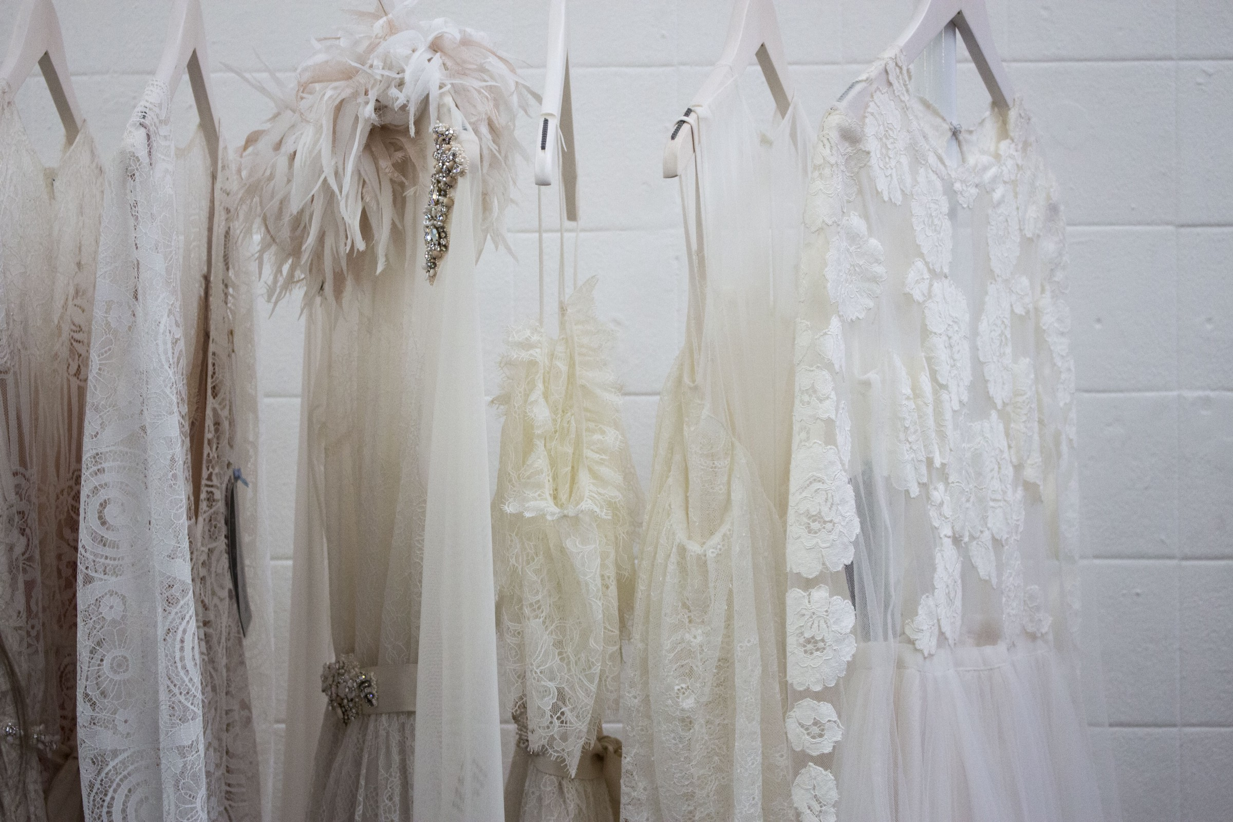 White dresses on white hangers against a white background.