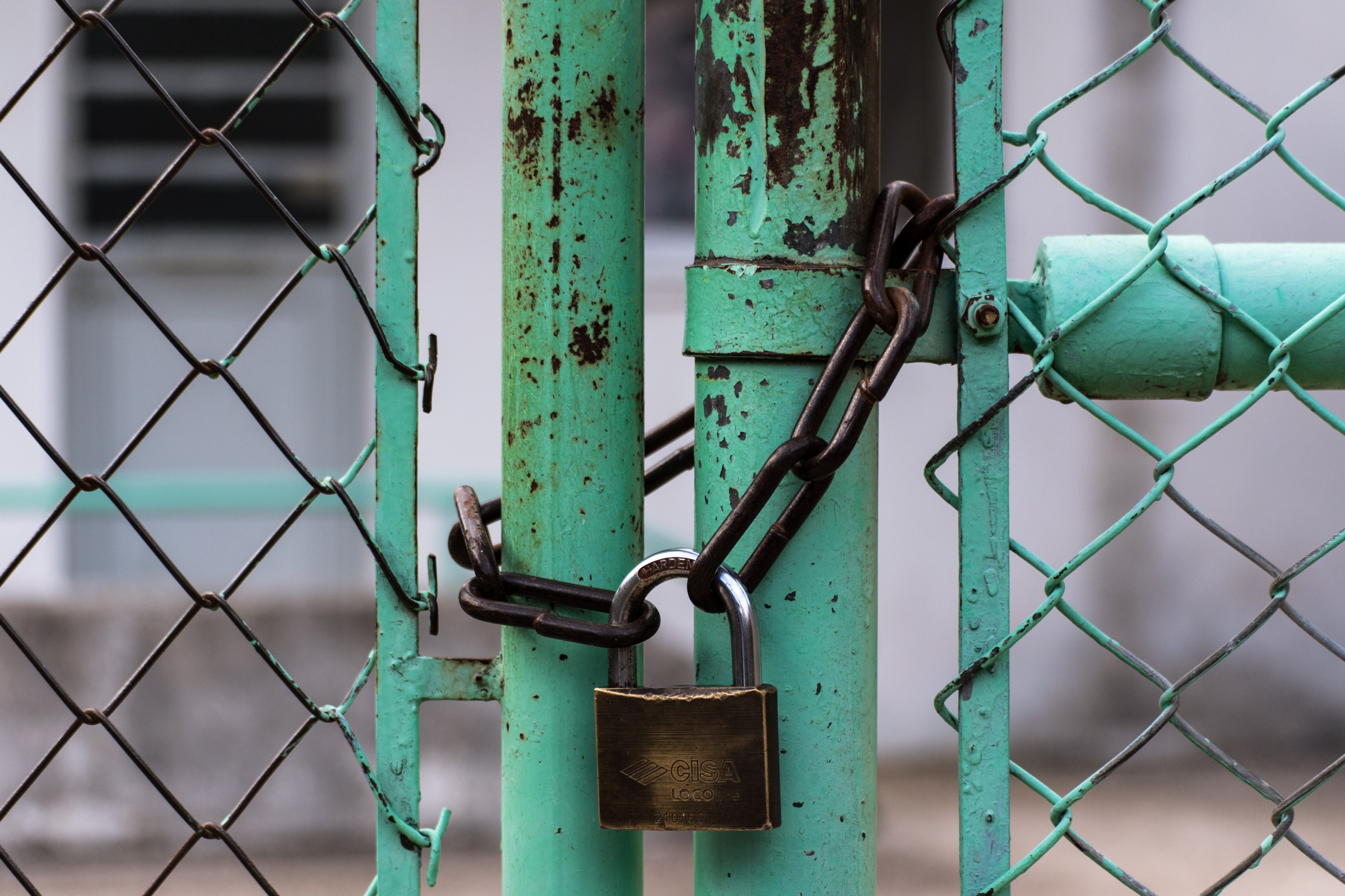 A green chainlink fence closed with a padlock. Photo by Jason Blackeye on  Unsplash