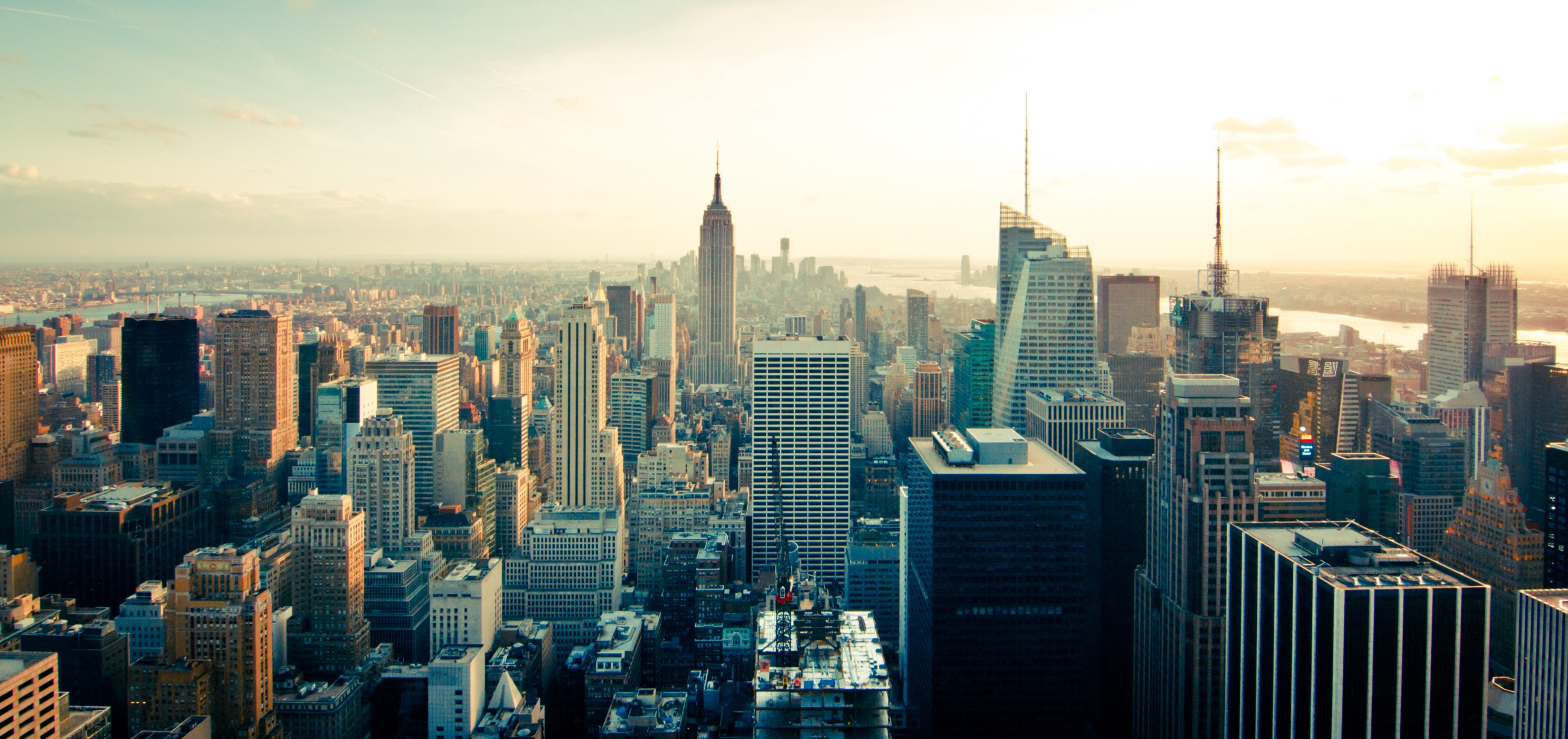 the new york city skyline with the empire state building at sunset by philipp henzler on unsplash