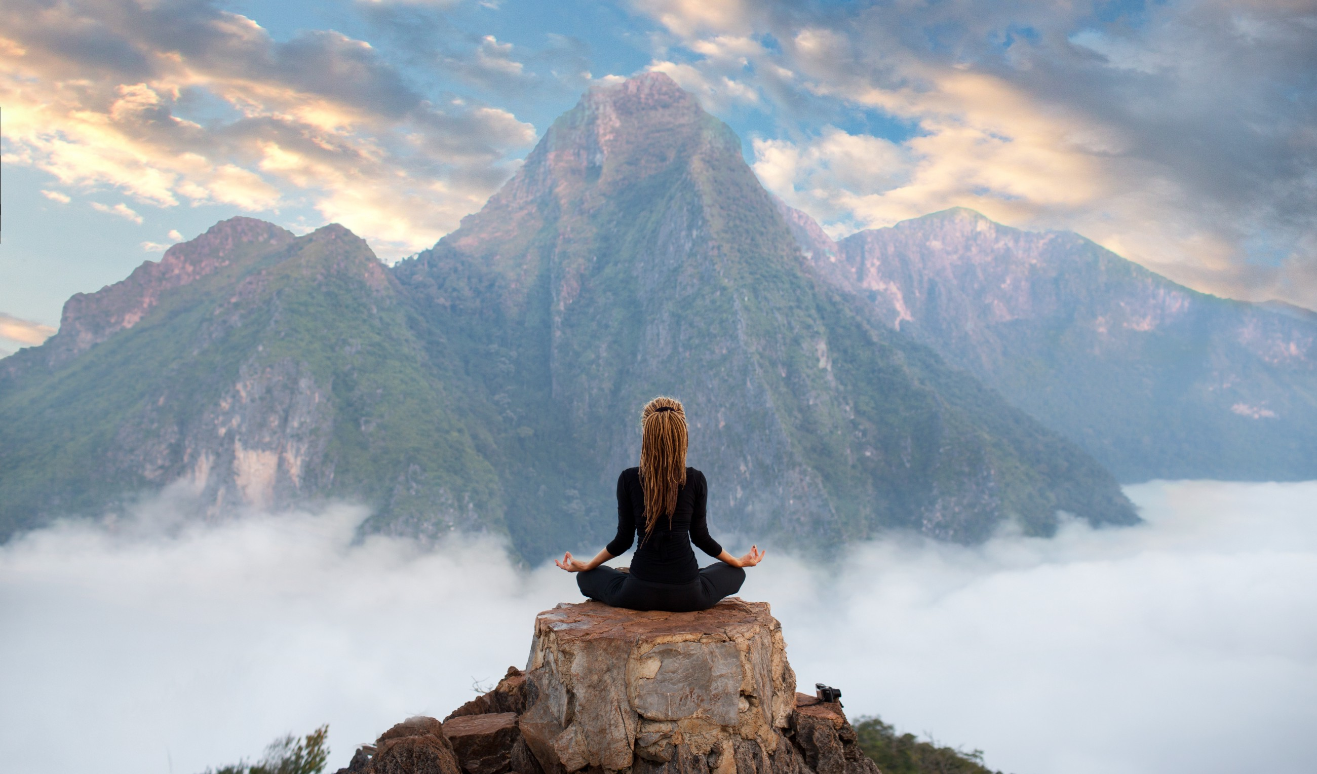 Woman meditating at the peak of mountain with other mountains around her.