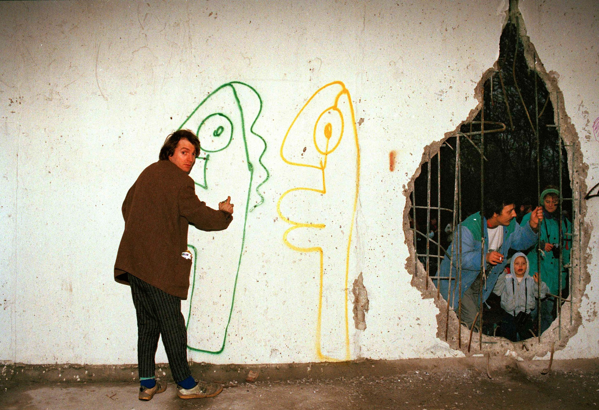 Thierry noir of west berlin sprays graffiti on the berlin wall in east berlin near the brandenburg gate jan 13 1990 before he could finish the job