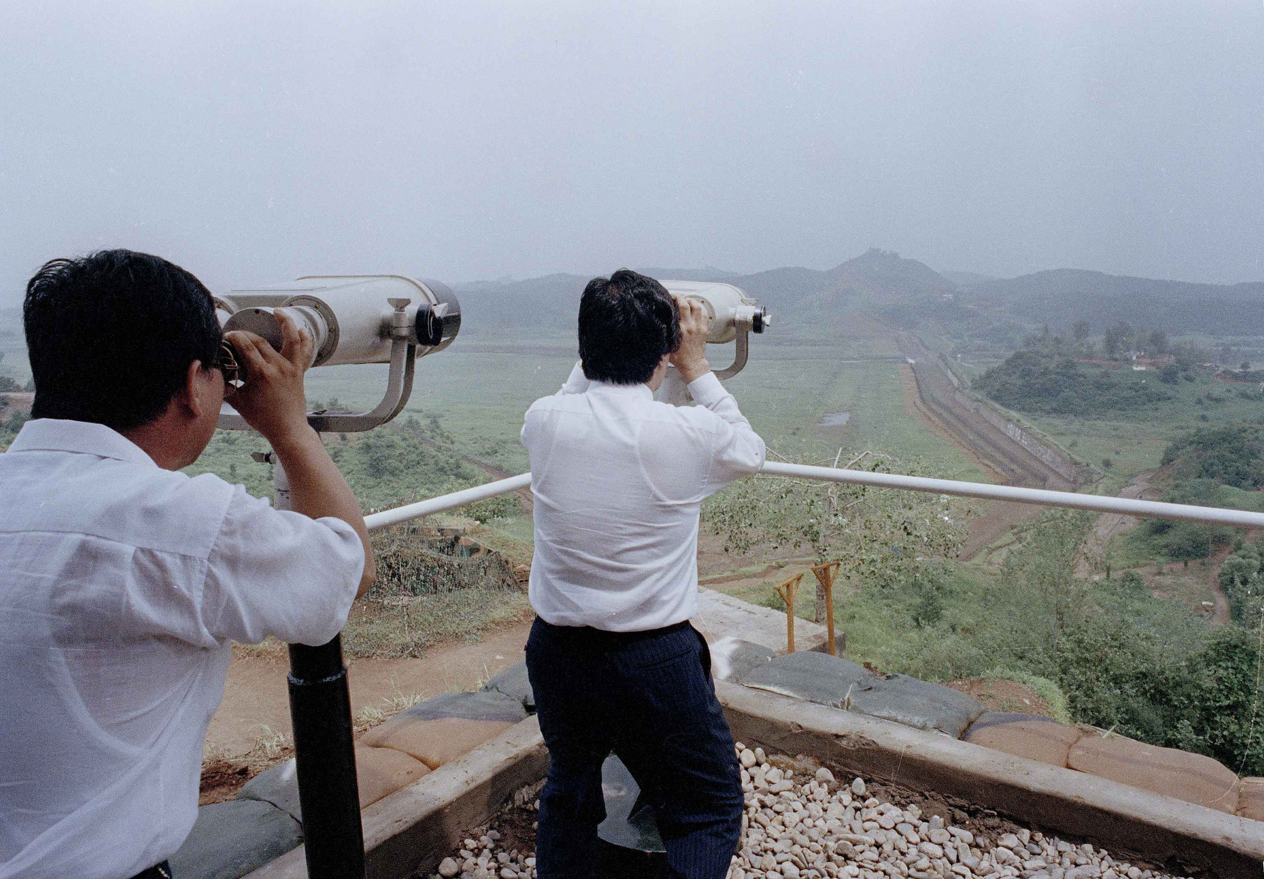 South Korean citizens look out at an anti-tank barrier built by South Korea  along the Korean Demilitarized Zone (DMZ) between North and South Korea 7f8381701