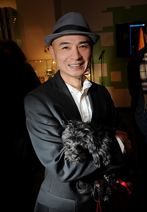 Smiling man wearing a fedora holding a small black dog.