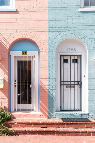 two almost identical front doors to two almost identical brick houses
