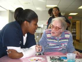 Young nurse sitting with older woman who_s painting water color images.