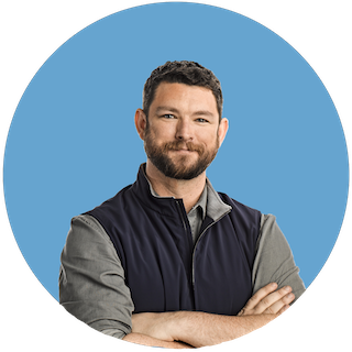 A headshot of Philip Martin, Coinbase CSO, smiling in a grey button-up and navy quarter-zip vest