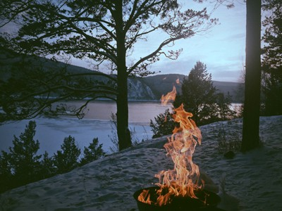 Camp fire with high flames set in the woods with a river running in the distance.
