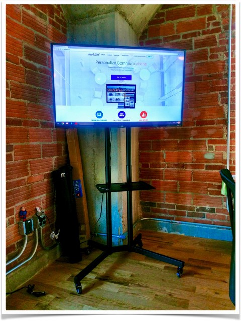 A flatscreen tv on a rolling stand in a modern office