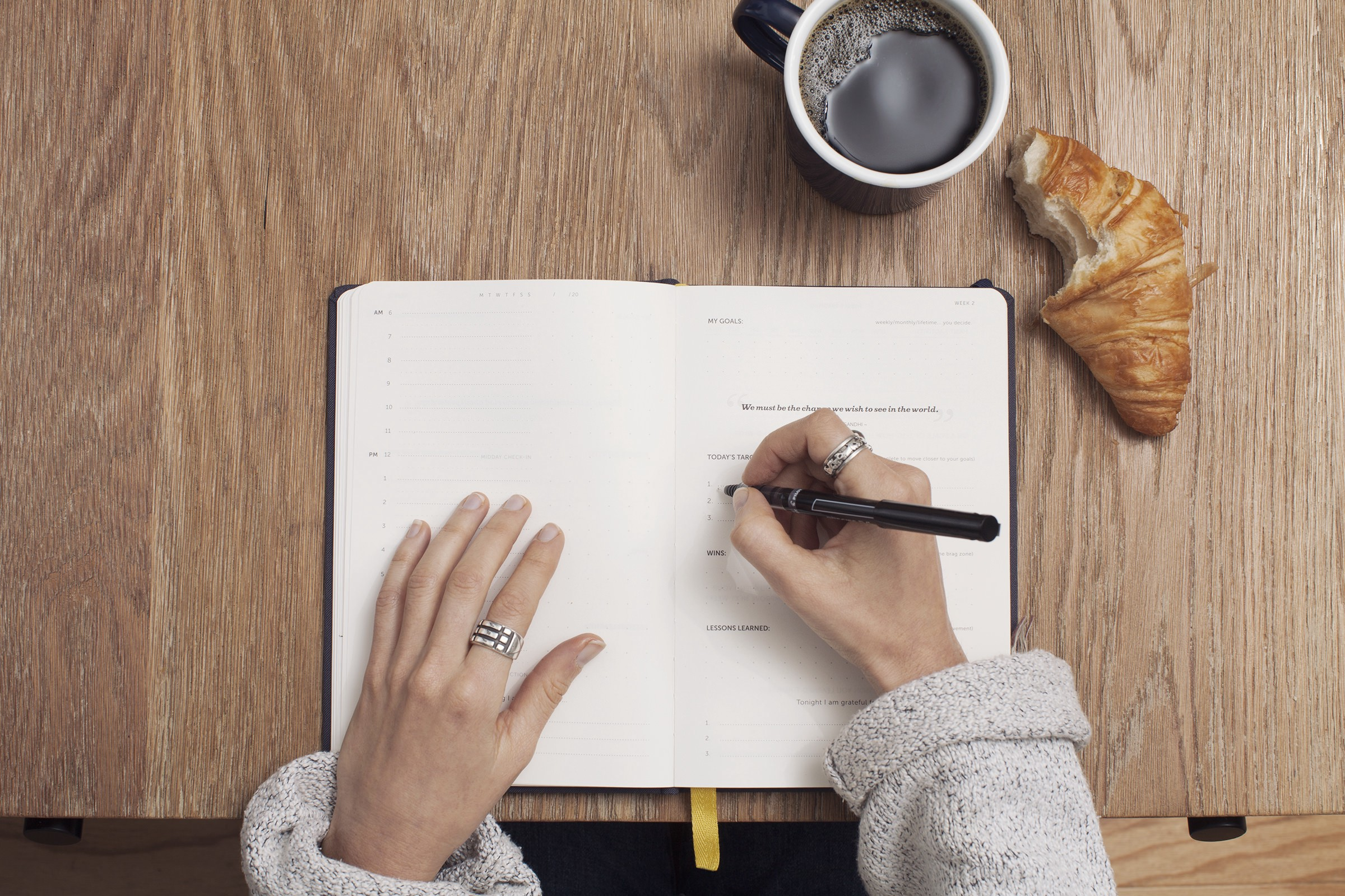 """""""A person writing in a life planner with a coffee and a croissant on the desk"""" by Cathryn Lavery on Unsplash"""