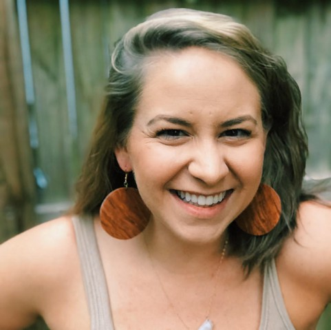 A portrait of Jess Budnick. She is a white woman smiling with brunette wavy hair and large brown wood circle earrings.