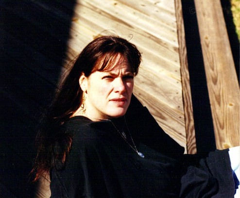 The author sitting on a deck with her face looking towards the camera.
