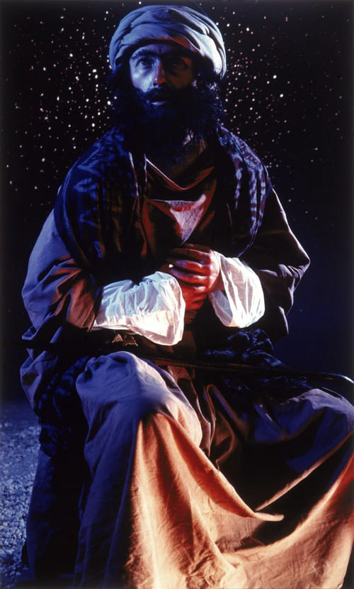 Full body portrait of biblical man at night dressed in red and white robes and white head wrap. The scene is lit in blue.