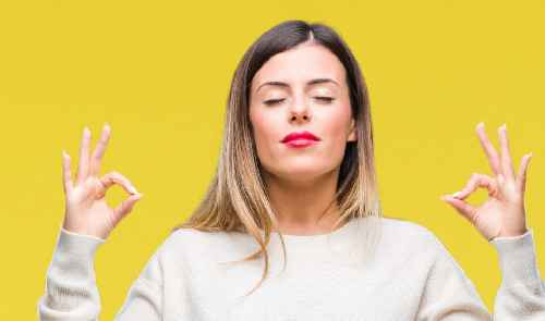 woman on yellow background with eyes closed in zen-like state