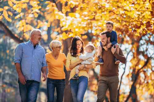 family with two parents, two kids, and two grandparents walking in front of autumn leaves