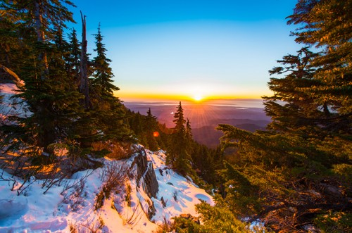 A view of a winter landscape in the wilderness with the sun setting.