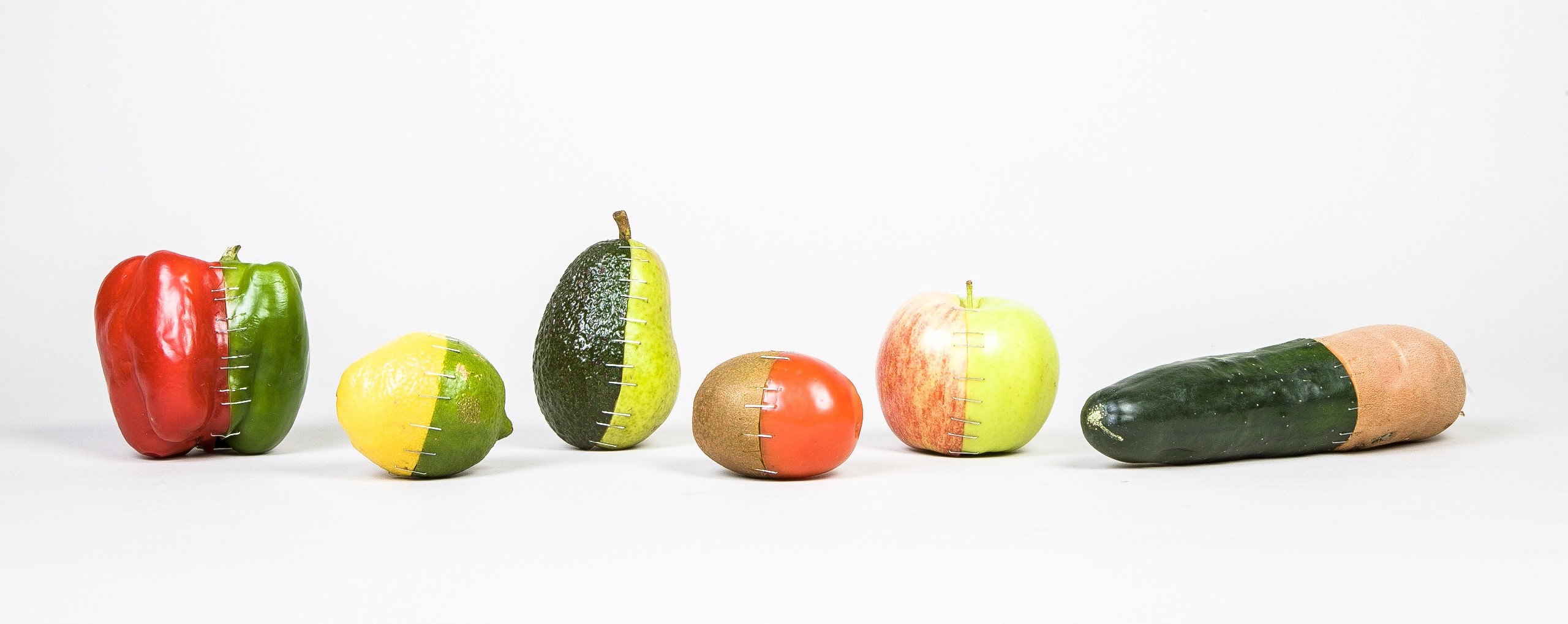 A collection of fruits and vegetables that have been cut in half and stapled back together differently, appearing like 2-part wholes of different items.