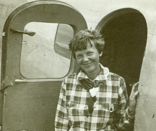 Amelia Earhart posing in front of a plane.