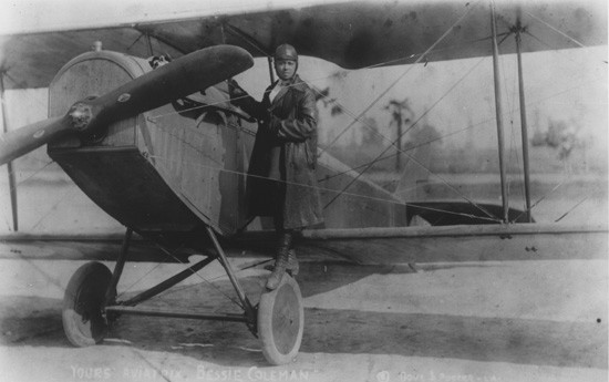 Bessie Coleman posing with her plane.