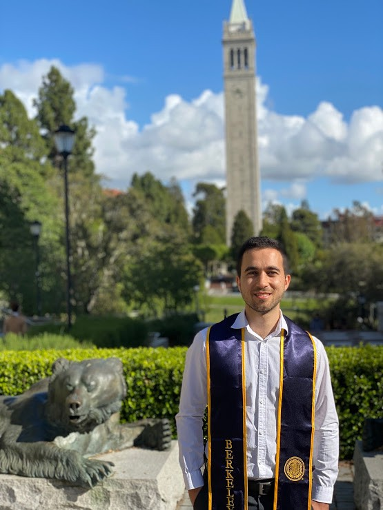 Young man posing with a navy stole with the Campanile in the background.