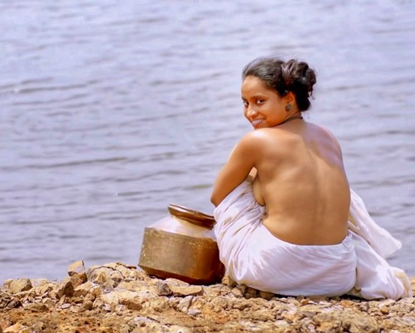 A semi- nude lady sitting on the banks of a river