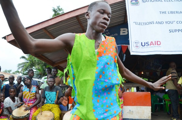 A Liberian boy wearing brightly colored clothing dances in front of a group of boys with drums.