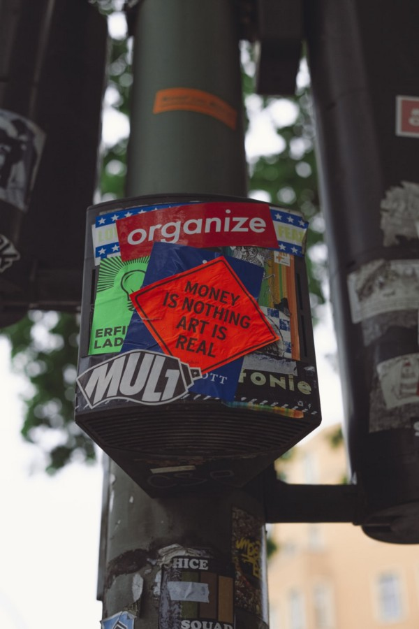 """Stickers on pole- One says """"Organize"""". Another in red- """"Money is Nothing, Art is Real"""""""
