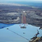 Suncor's Millenium tailings pond dredge barge and oil slick boom