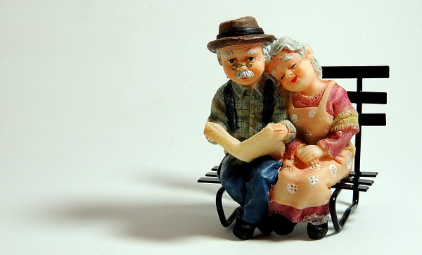 Ceramic figurines of old couple on a bench.