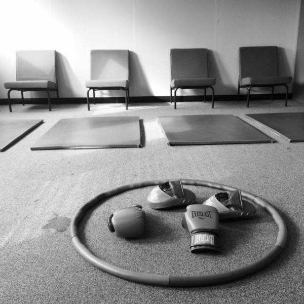 A photo of gym mats laid out on the floor with a hula hoop and boxing mitts in the foreground