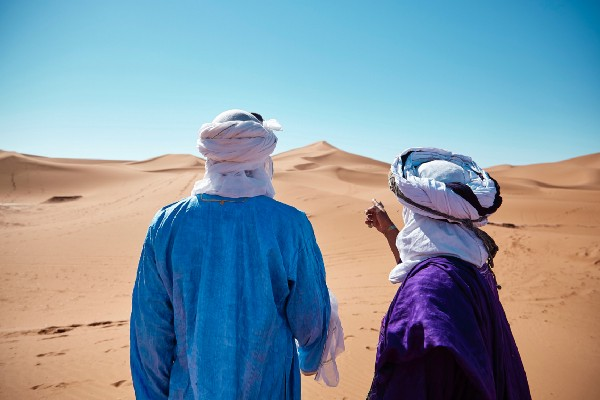 Image of two men in the desert, one directing the other