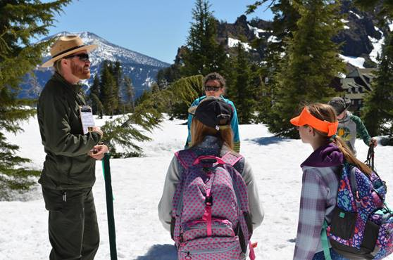 A man wearing a park ranger's hat stands on a snow-topped hill talking to a group of four children