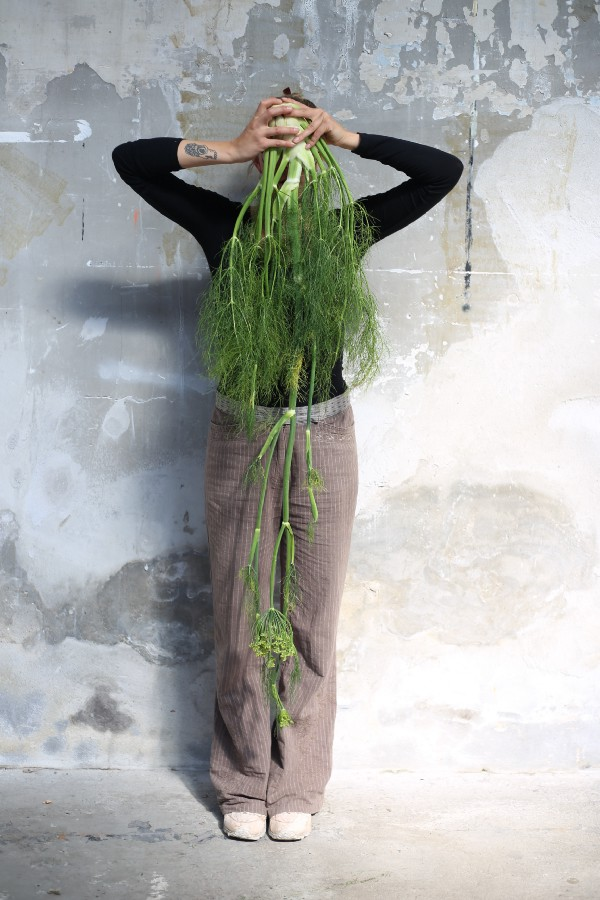 A person hiding behind a long fennel plant