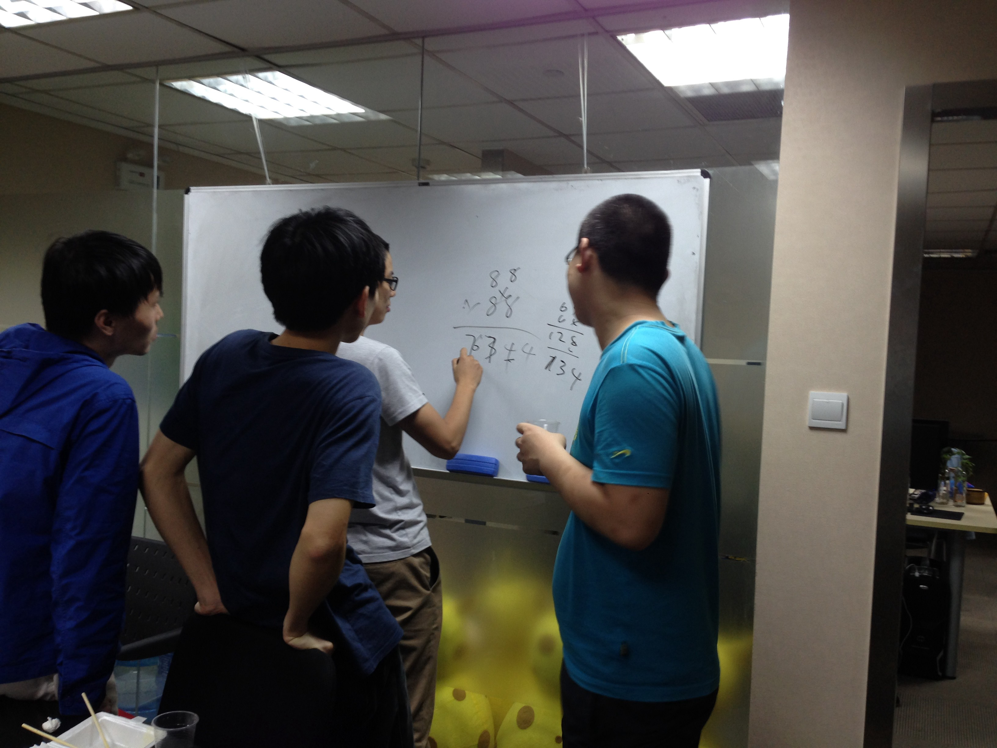 A late night debate between our head of QA (holding marker) and CTO (right) about the fastest way to multiply large numbers mentally