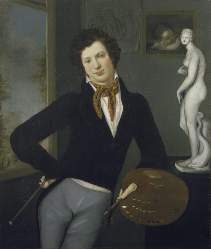 19th century man standing in contrapasso proudly displaying an artist's palette & paint brushes. Behind him is more artwork.