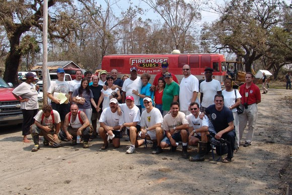 A group of volunteers including Firehouse Subs co-founders, Chris Sorensen and Robin Sorensen, pose for a photo in front of Fire-ONE (the Firehouse Subs bus) after Hurricane Katrina.