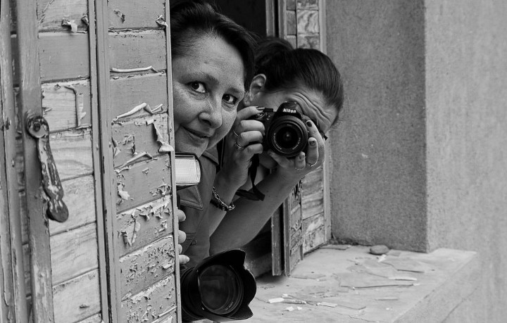two women looking out of window taking a photo