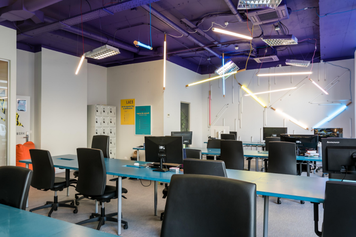 Colourful space at LACS equipped with multiple chairs at shared desks