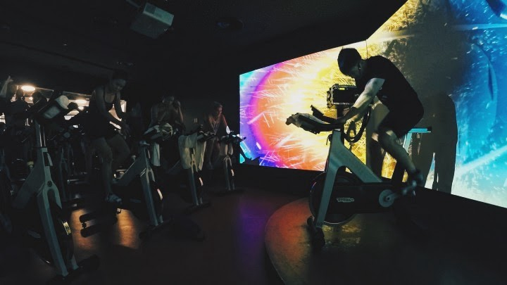 Indoor cycling studio with projected visuals on walls