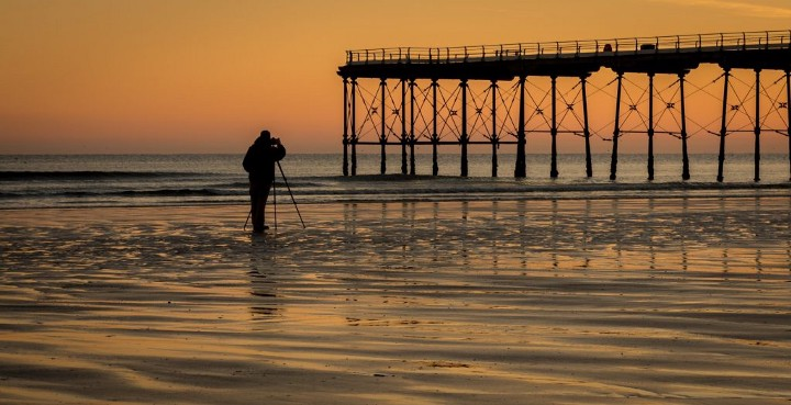 sunset on the beach with man taking photo
