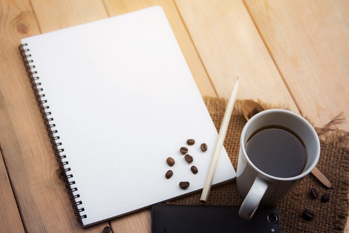 Notebook and coffee cup, with coffee beans inexplicably scattered upon notebook