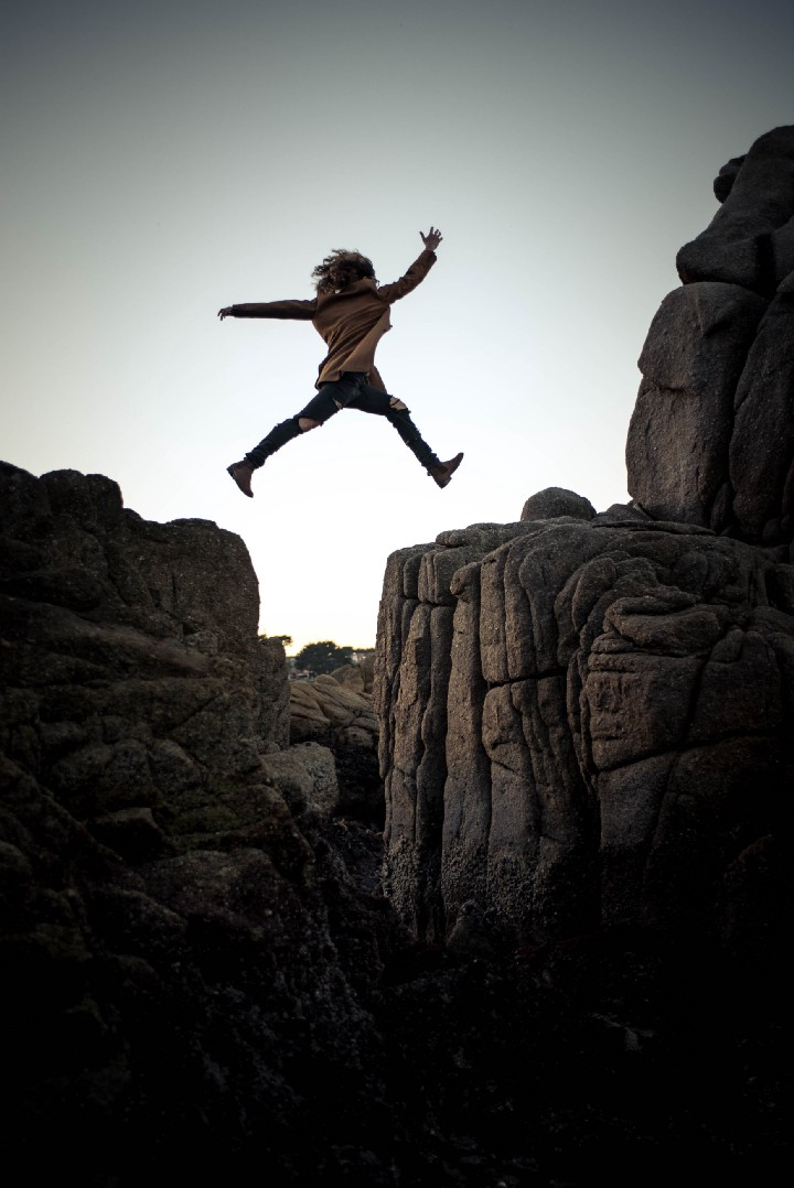 Man jumping across gap between two cliffs