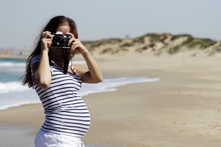 Pregnant Woman on Beach Taking Photos