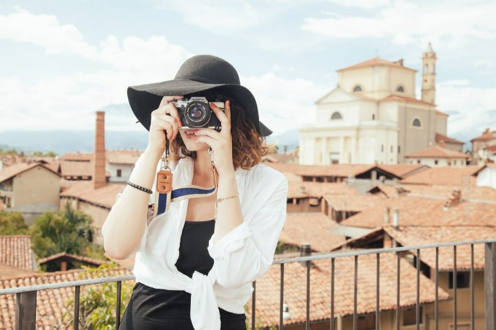Woman in hat taking photo with a dslr camera