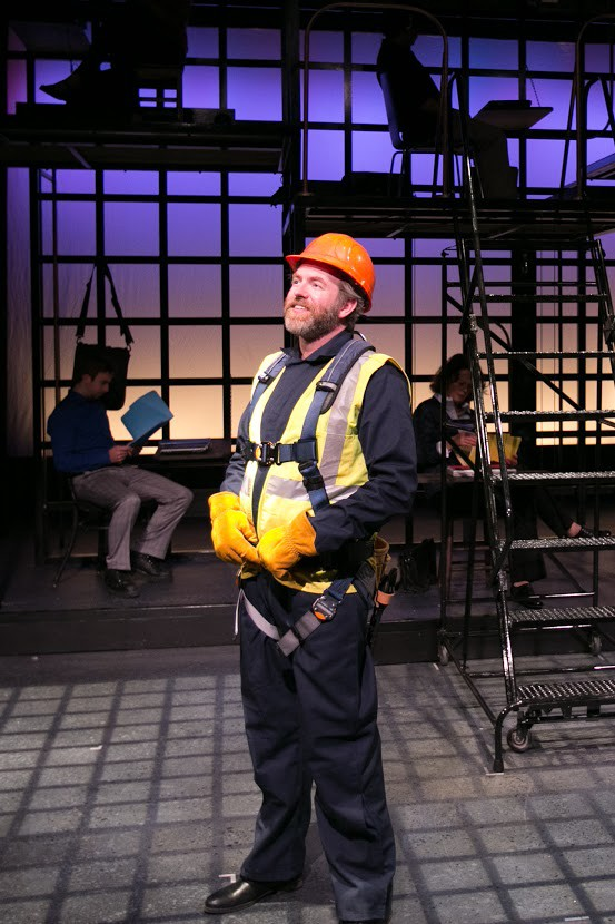 Christopher Chew in a construction workers outfit with Phil Tayler and Shannon Lee Jones working in the background