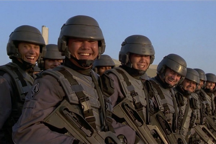 """A still from """"Starship Troopers,"""" showing rows of grinning soldiers."""