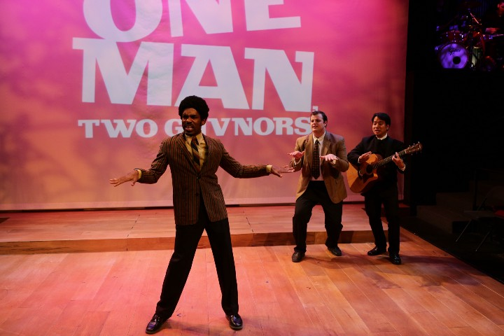 Davron Monroe dancing in the middle of the stage with  Harry McEnenerny and Chuong Plham in the background in One Man, Two Guvnors