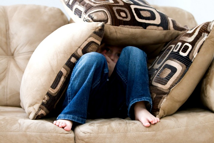 Photo of person under a pile of cushions