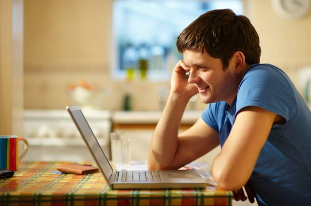 Young man using laptop at kitchen table